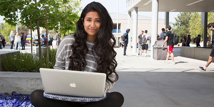 Female student sitting in the quad with computer